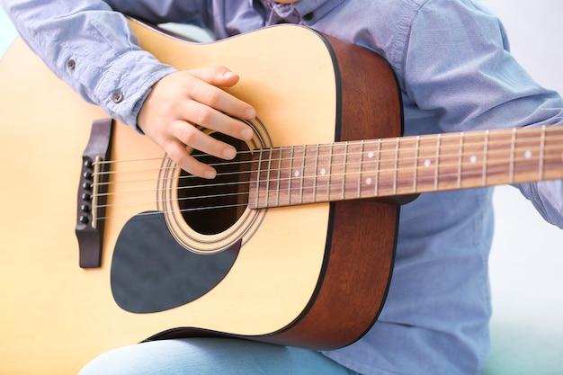 Kleiner junge, der zu hause gitarre spielt, nahaufnahme