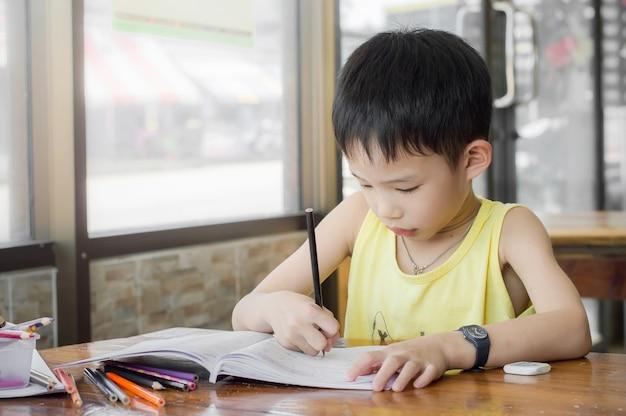 Kleiner junge, der zu hause hausarbeit für schule auf dem schreibtisch tut