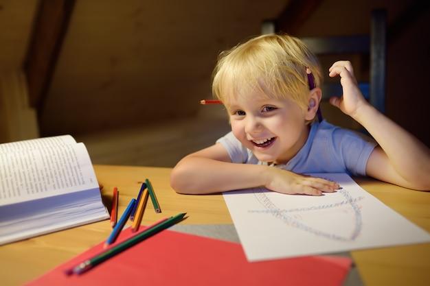 Kleiner junge, der zu hause hausarbeit tut, malt und abend schreibt. vorschulkind lernen lektionen - zeichnen und farbbild. kindertraining zum schreiben und lesen.