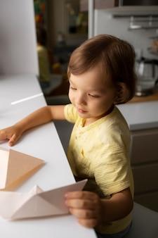 Kleiner junge, der zu hause mit origami-papier spielt