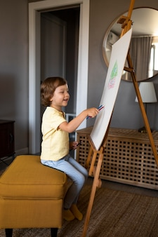 Kleiner junge, der zu hause mit staffelei zeichnet