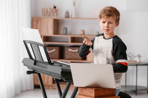 Kleiner junge, der zu hause online musikunterricht nimmt
