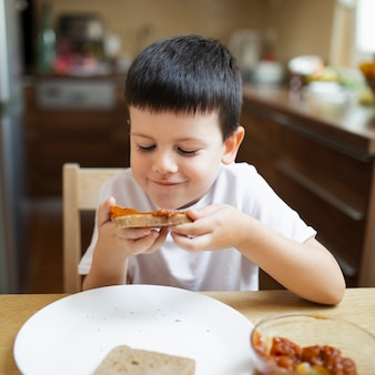 Kleiner junge, der zu hause snack isst