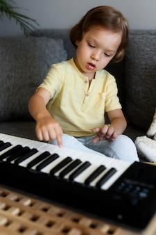 Kleiner junge, der zu hause tastatur spielt
