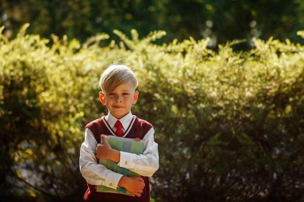 Kleiner junge, der zurück zur schule geht. kind mit rucksack und büchern am ersten schultag