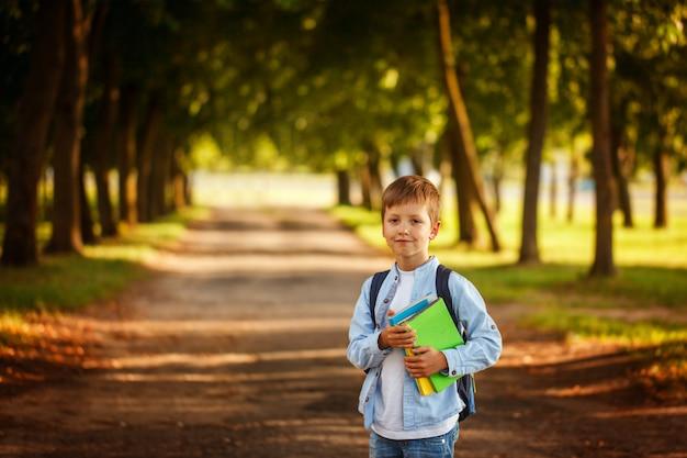 Kleiner junge, der zurück zur schule geht. kind mit rucksack und büchern.