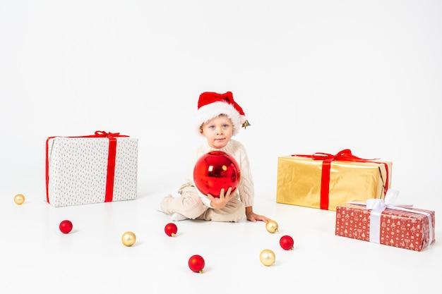 Kleiner junge, der zwischen geschenken sitzt und großen roten weihnachtsball in den händen hält. isoliert auf weißem hintergrund feiertage, weihnachten, neues jahr, weihnachtskonzept.