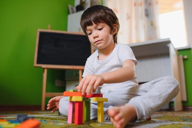 Kleiner junge des kindes, der mit holzwürfelspielzeugen im kinderzimmer zu hause oder in der kindertagesstätte spielt