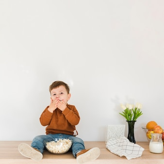 Kleiner junge des porträts, der popcorn isst
