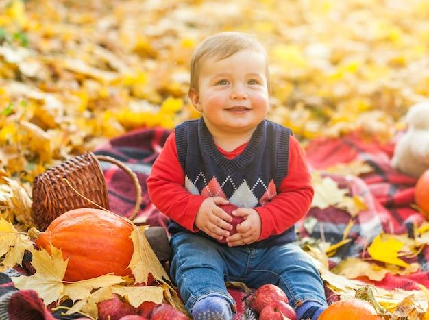 Kleiner junge des smiley, der auf einer decke sitzt