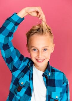 Kleiner junge des smiley, der mit seinen haaren spielt