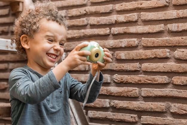 Kleiner junge draußen mit kameraspielzeug
