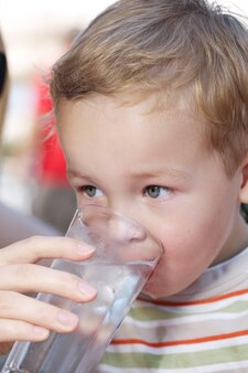 Kleiner junge drinkng ein glas süßwasser