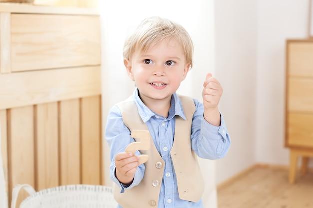 Kleiner junge. ein fröhlicher und lächelnder junge hält eine figur in seinen händen. kind im kindergarten. porträt des modernen männlichen kindes. lächelnde jungenaufstellung. konzept der kinder stil und mode. skandinavisch