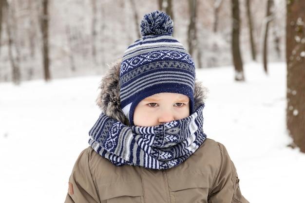 Kleiner junge, eingewickelt in einen schal mit einer mütze und gekleidet in warme winterkleidung, die im winter im park geht, nahaufnahme des winters bei frostigem wetter
