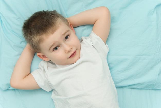 Kleiner junge erwacht in seinem bett