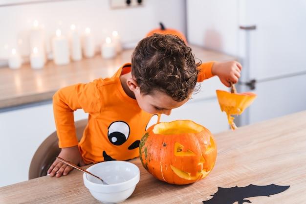 Kleiner junge gekleidet in einem halloween-kürbis-t-shirt, das einen halloween-kürbis und die dekoration öffnet und entleert...