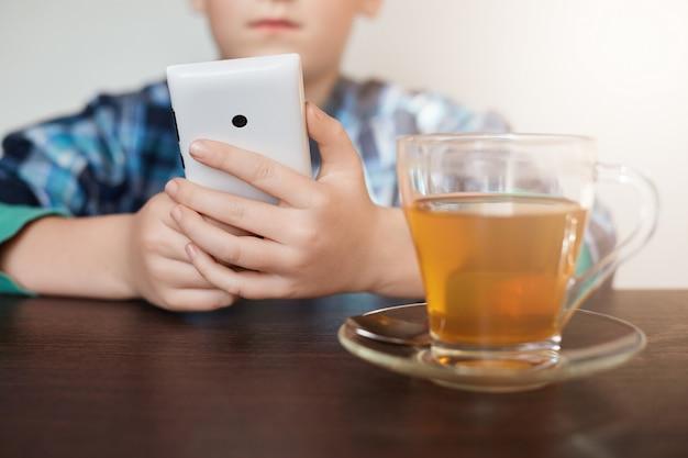 Kleiner junge gekleidetes kariertes hemd, das am tisch mit einer tasse tee sitzt, der smartphone in seinen händen hält, die spiele online spielen. technologie-smartphone