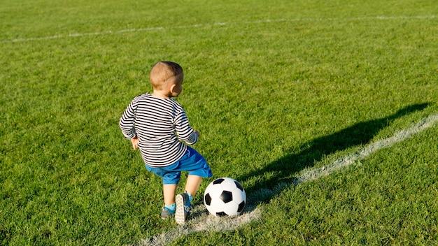 Kleiner junge genießt es, über ein grünes sportfeld zu rennen und ihm im abendlicht einen fußball zu treten