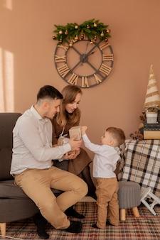 Kleiner junge gibt eltern eine geschenkbox. geburtstagsgeschenke . kleiner sohn mit seiner familie.