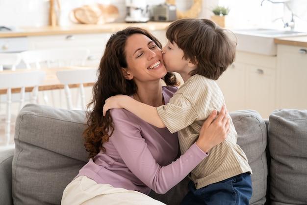 Kleiner junge gibt mama einen zärtlichen kuss in die wange, der die alleinerziehende mutter am muttertag umarmt oder zum geburtstag grüßt. süßer sohn von 5, der liebevolle mama umarmt, zeigt liebe und fürsorge. elternschaft und glückliches familienkonzept