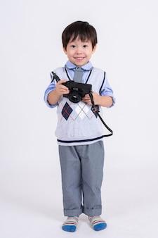Kleiner junge glücklich mit kamera auf weiß Kostenlose Fotos