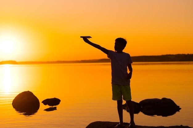 Kleiner junge hält bei sonnenuntergang ein papierflugzeug in der hand. ein kind hob seine hand zum himmel und spielt am abend mit origami am see. silhouette