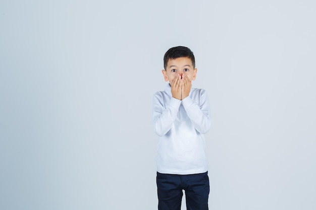 Kleiner junge hält die hände auf dem mund in weißem hemd, hose und schaut aufgeregt, vorderansicht.