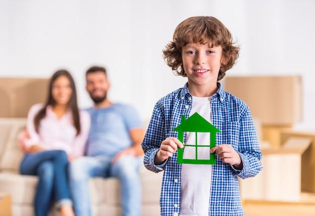 Kleiner junge hält ein papphaus in seinen händen.