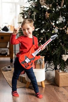 Kleiner junge hält eine gitarre