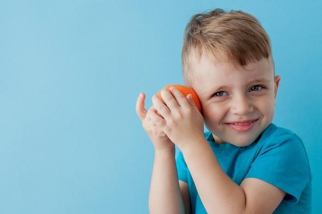 Kleiner junge hält eine orange in seinen händen auf blau, diät und bewegung für eine gute gesundheit