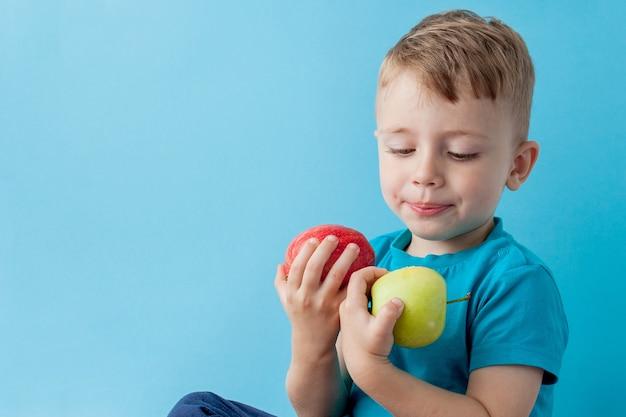 Kleiner junge hält einen apfel in seinen händen auf blau, diät und bewegung für eine gute gesundheit