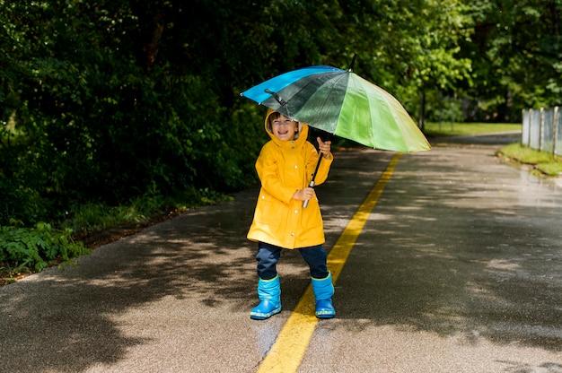 Kleiner junge hält einen regenschirm