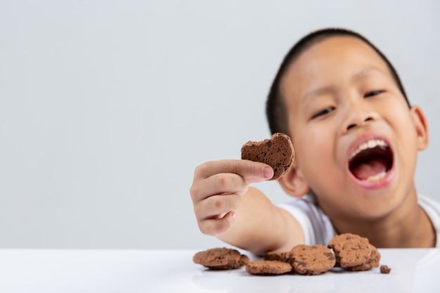 Kleiner junge hält keks, der am tisch auf weißer wand essen möchte.