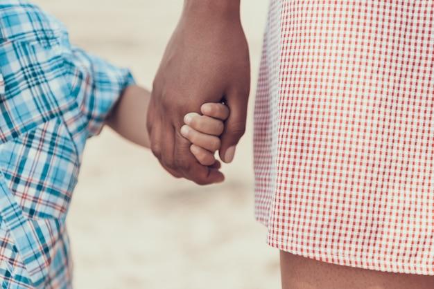 Kleiner junge hält papa an der hand am strand