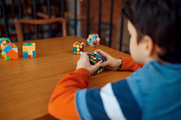 Kleiner junge hält puzzlewürfel, selektiver fokus zur hand. spielzeug für gehirn- und logisches denktraining, kreatives spiel, lösung komplexer probleme