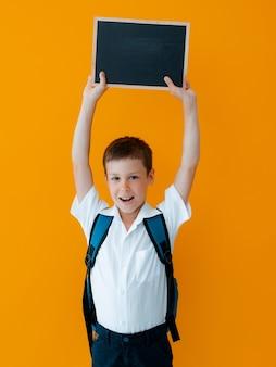 Kleiner junge hält schultafel auf gelbem hintergrund. kleine schuluniform mit rucksack mit leeren händen. tafel für werbung, kopienraum. für ihre aufmerksamkeit.
