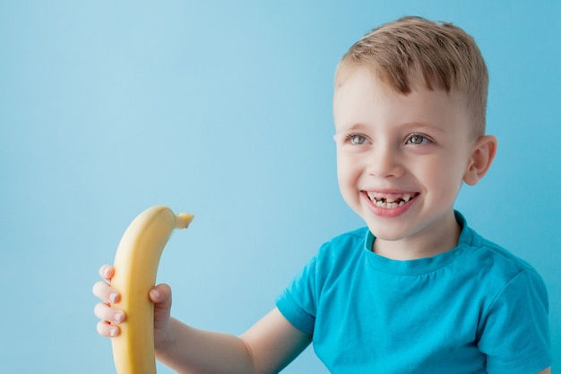 Kleiner junge hält und isst eine banane