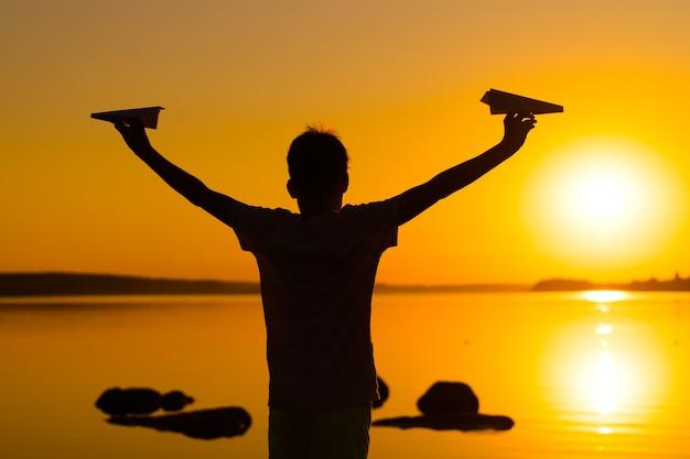 Kleiner junge hält zwei papierflugzeuge in ausgebreiteten händen. junge spielt bei sonnenuntergang auf dem seehintergrund. zeit im freien. schwarze silhouette gegen sonnenuntergang