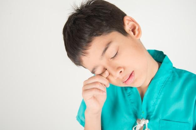 Kleiner junge hat augenschmerzen mit fingerkratzer