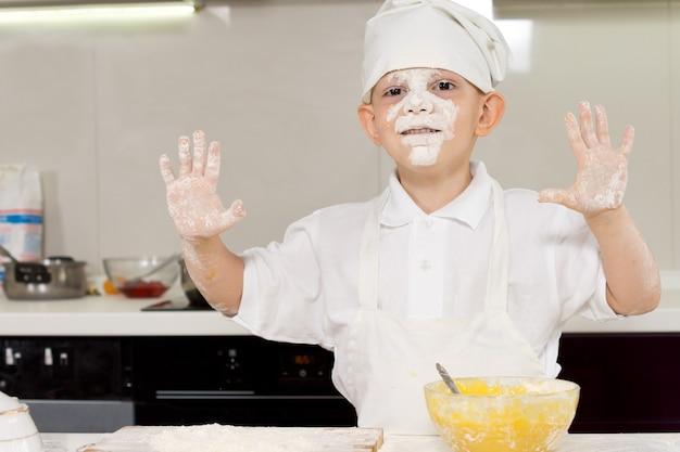 Kleiner junge hat spaß beim kochen in der küche