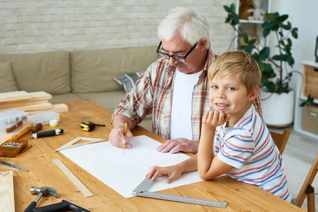 Kleiner junge hilft opa, vogelhaus zu machen