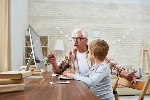 Kleiner junge hört opa am computertisch zu