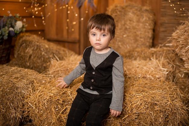 Kleiner junge im bauernhof, der in strohgarben, landschaft, landwirtschaft spielt