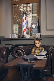 Kleiner junge im friseursalon im wartezimmer wartet auf meister