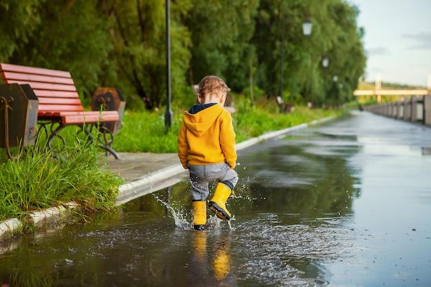 Kleiner junge im gelben regenmantel, der in den pfützen spielt