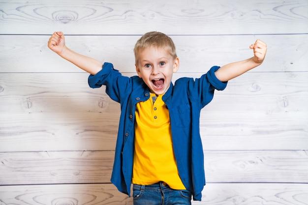 Kleiner junge im gelben t-shirt und im blauen hemd, die glück mit geöffnetem mund zeigt. lächelndes kind mit dem ausbreiten seiner hände