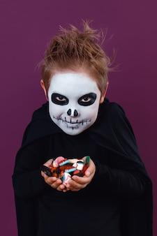 Kleiner junge im halloween-kostüm hält süßigkeiten auf violettem hintergrund in die kamera. halloween-make-up.