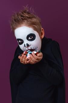 Kleiner junge im halloween-kostüm hält süßigkeiten und behandelt sie auf violettem hintergrund. halloween-make-up.