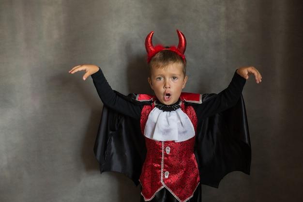 Kleiner junge im halloween-vampir-kostüm auf grauer wand. emotionskind.